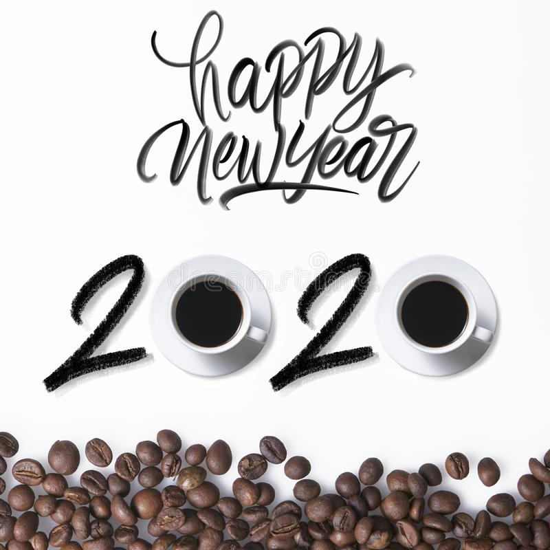 Happy new year 2020 coffee. Happy new year 2020 hand latter an ordinary concept with cups of coffee and coffee beans on white royalty free stock photo